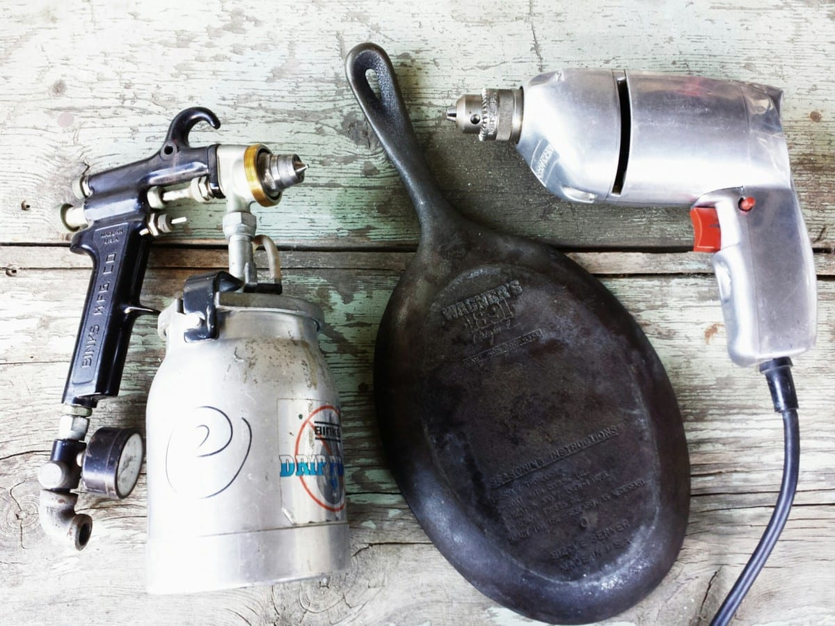 Paint gun, old cast iron skillet, and an old silver metal drill
