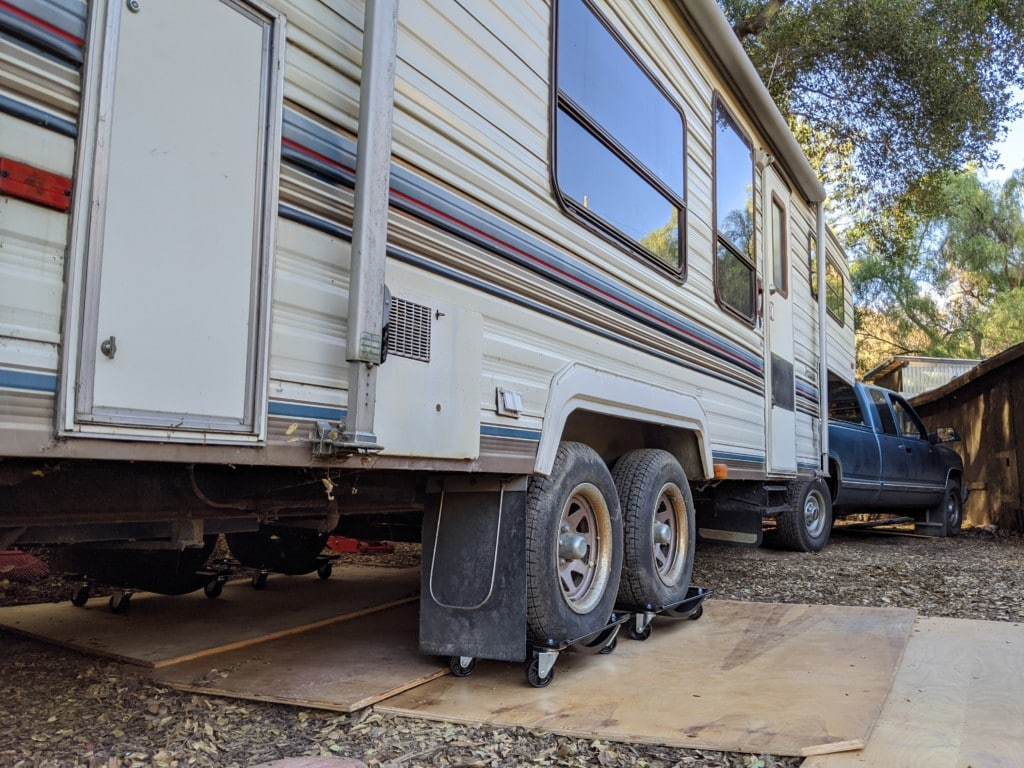 Fifth wheel trailer with it's tires on casters, hitched to a blue chevy truck